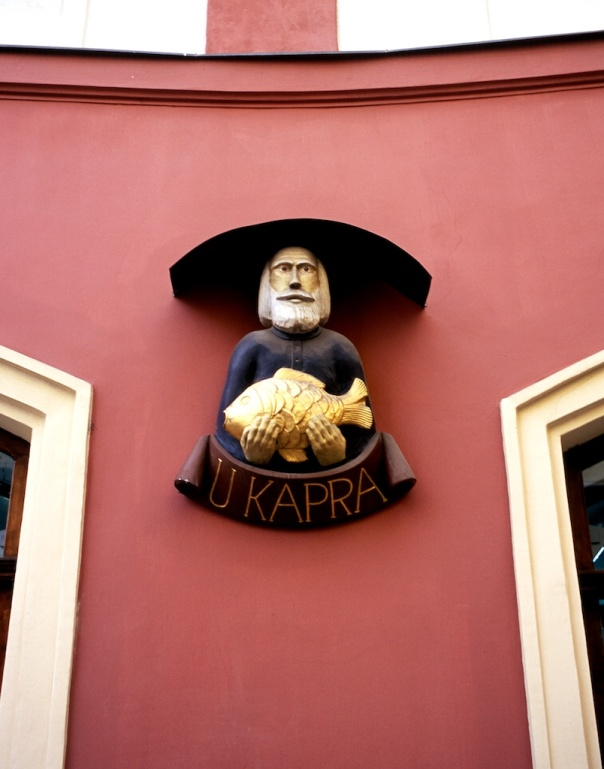 Building facade of man holding fish, Prague