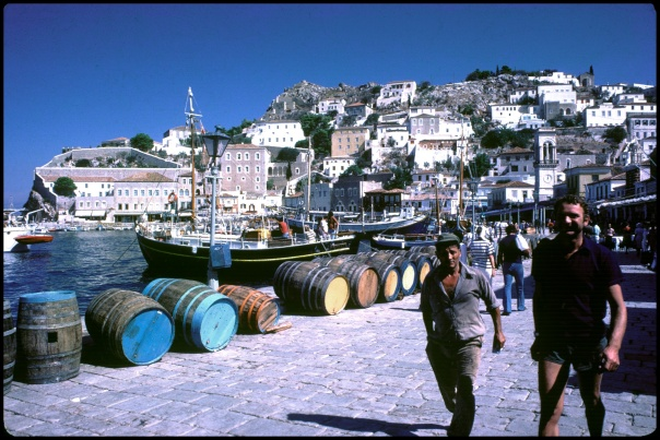 Men walk past barrels on Greek Isle